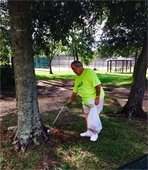 Councilman George Wolverton wearing a bright green shirt picking up trash in a park