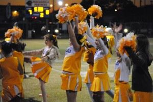 Cheerleaders in yellow outfits with pom poms, side view