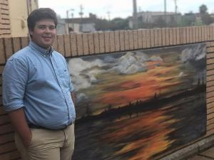 Young White boy standing in front of a sunset mural