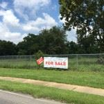 Image of field with wire fence around it, and a sidewalk, and a for sale sign on fence